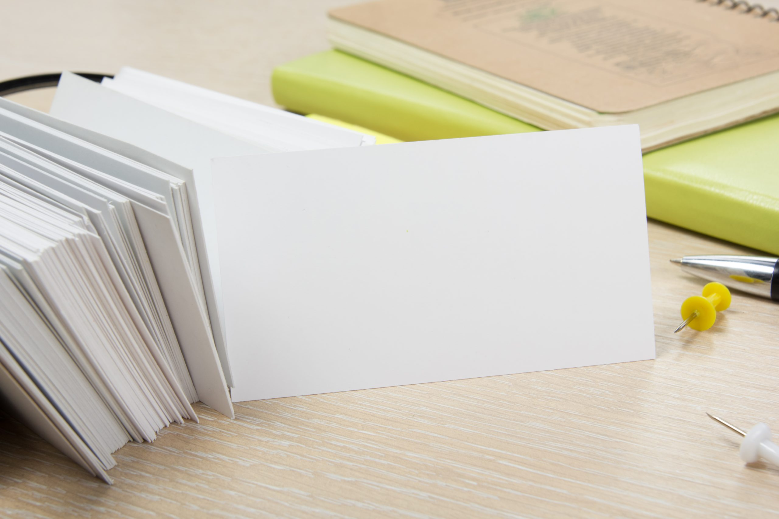 White blank business card. Office table desk with set of colorful supplies, cup, pen, pencils, flower, notes, cards on beige desk table background. Top view and copy space for ad text